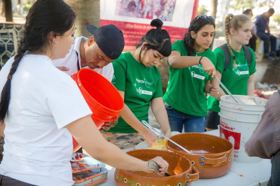 Voluntarias y personal de Projects Abroad sirviendo comida a gente sin hogar durante un día comunitario en México.